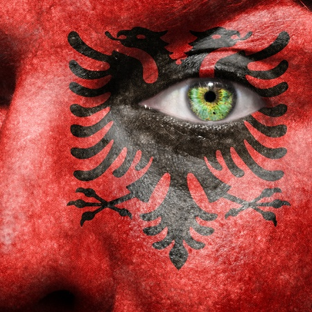 Flag painted on face with green eye to show Albania support photo