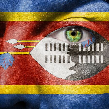 Flag painted on face with green eye to show Swaziland support Stock Photo - 14981120