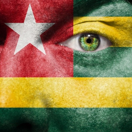 Flag painted on face with green eye to show Togo support photo