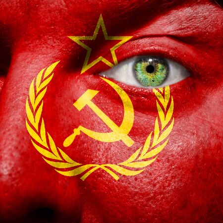 Flag painted on face with green eye to show USSR support photo