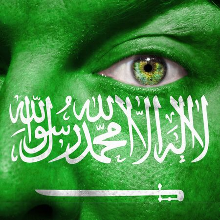 Flag painted on face with green eye to show Saudi Arabia support Stock Photo