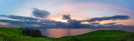 Panoramic view from Dunluce Castle of the atlantic ocean and the sun setting over the Skerries Islands at Portrush Stock Photo