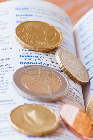 Many euro coins lying on a dictionary page next to the word finance photo