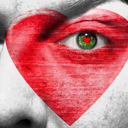 Red heart painted on white face with heart shaped red pupil in a green eye photo