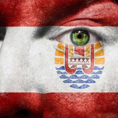 Flag painted on face with green eye to show Tahiti support Stock Photo - 15502593