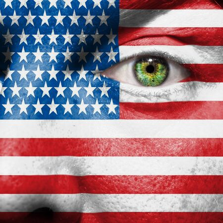 Flag painted on face with green eye to show USA support photo
