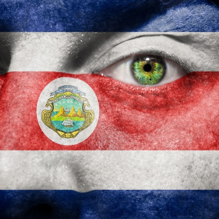 costa rican: Flag painted on face with green eye to show Costa Rica support