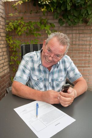 Extremely happy senior signing a document in his backyard photo