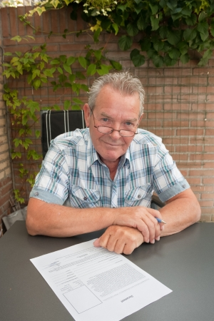 Senior about to sign legal document in his backyard Stock Photo