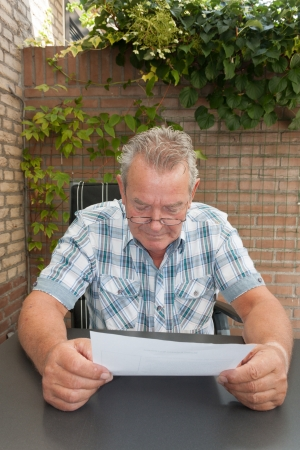 Serious looking senior man reading a document in his backyard photo