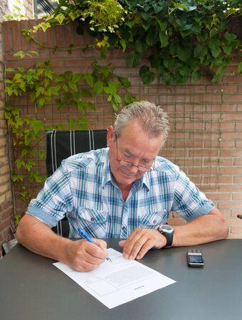 Senior ondertekening van een juridisch document en een mobiele telefoon op de tafel in zijn achtertuin