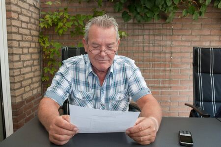 Happy Senior smiling and reading a document with a mobile phone on the table photo