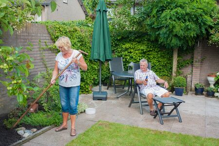 actively: Actively retired Dutch seniors in a Typical display of gender roles where the Wife is gardening and the husband is relaxing and having a beer