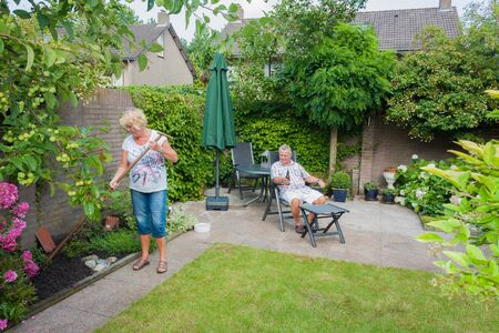 Actively retired Dutch seniors in a Typical display of gender roles where the Wife is gardening and the husband is relaxing and having a beer photo