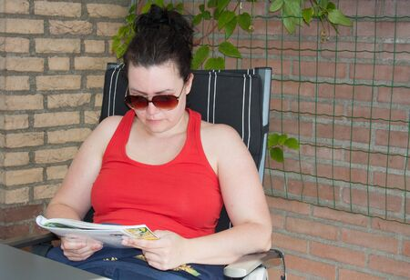 dutch girl: Woman wearing red tank top and sunglasses is reading a magazine