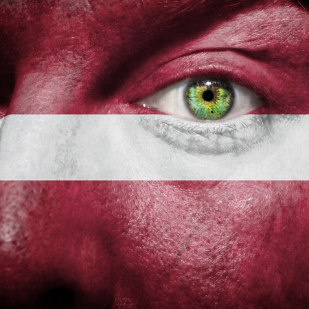burgundy background: Flag painted on face with green eye to show Latvia support