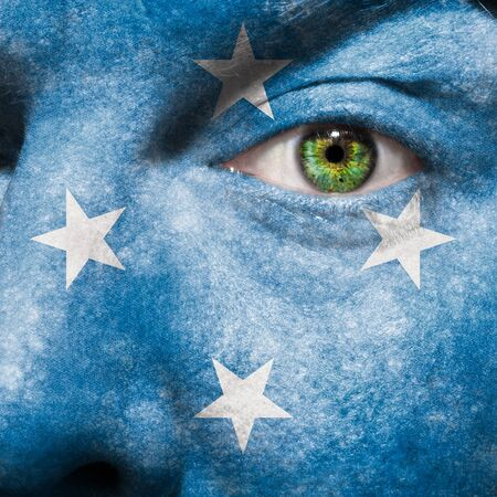Flag painted on face with green eye to show Micronesia support photo