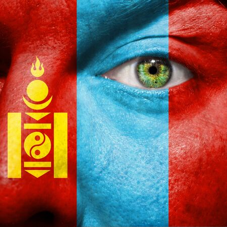 Flag painted on face with green eye to show Mongolia support photo
