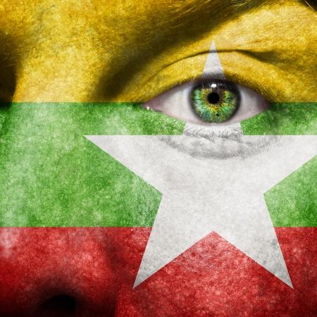 Myanmar: Drapeau peint sur le visage avec des yeux verts pour montrer le soutien Myanmar