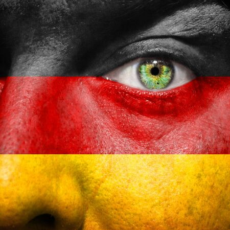Flag painted on face with green eye to show Germany support photo