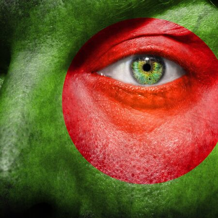 Flag painted on face with green eye to show Bangladesh support photo