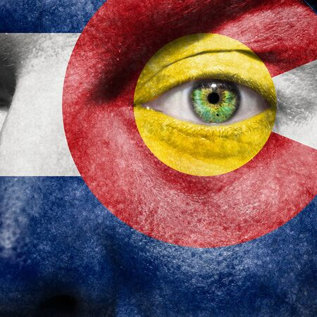 Flag painted on face with green eye to show Colorado support photo