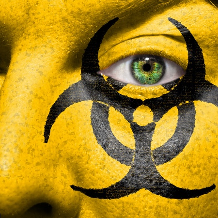 Biohazard symbol painted on face with green eye to raise awareness for bio hazardous waste photo