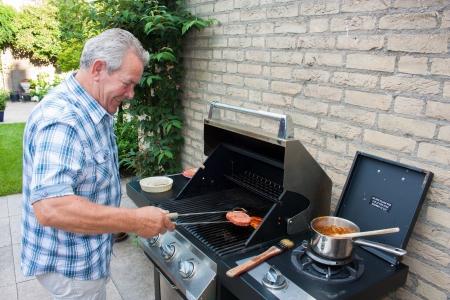 夏の日に彼の裏庭でハンバーガーを焼くオランダ シニア男を引退 写真素材 - 15812408