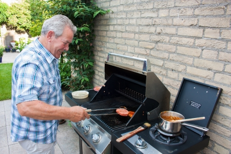 backyards: Retired dutch senior man grilling hamburgers in his back yard on a summer day