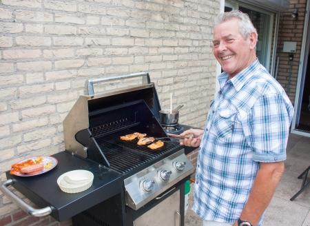 Gepensioneerde Nederlandse senior man grillen hamburgers in zijn achtertuin op een zomerse dag
