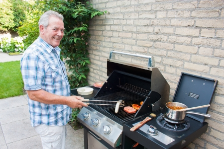 Retired dutch senior man grilling meat in his back yard on a summer day Stockfoto