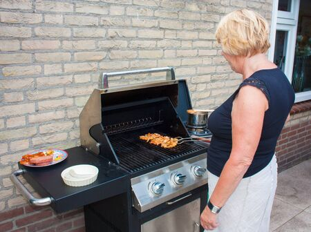 Retired dutch senior woman grilling pork chops in her back yard on a summer day photo