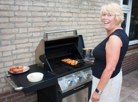 gas cooker: Retired dutch senior woman grilling pork chops in her back yard on a summer day