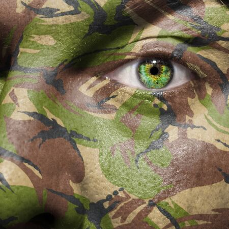 guerrilla warfare: Camouflage painted on a face with green eye to portray military personal or guerrilla