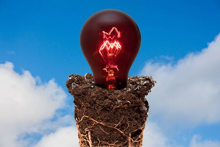 soil conservation: Earth and red light bulb against blue cloudy sky