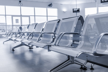 Airport gate waiting area with metal seats in monochrome photo
