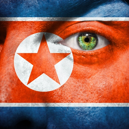 Flag painted on face with green eye to show south korea support photo