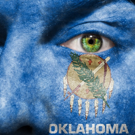 Flag painted on face with green eye to show Oklahoma support photo