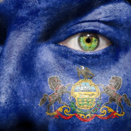 Flag painted on face with green eye to show Pennsylvania support Stock Photo