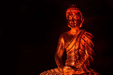 gautama: Gautama Buddha in warm light against dark background