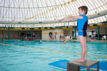 Weinig jongen in zwembad dragen blauwe zwemvest klaar om een duik te nemen