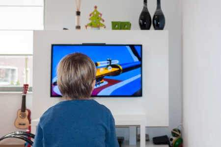 Little child watching a cartoon on a HD flat screen TV in a modern living room with toys Banque d'images