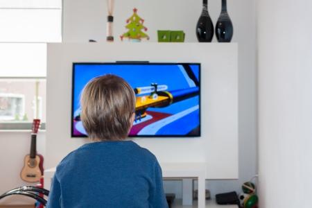 viewing: Piccolo bambino guardando un cartone animato su un televisore a schermo piatto HD in un moderno salotto con i giocattoli
