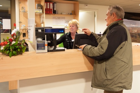 operated: Senior man purchasing museum pass at front desk operated by a senior female volunteer cashier
