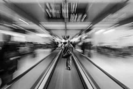国際空港のエスカレーターで急いでゲートに男