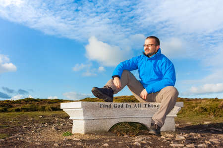 reverence: Male hiker sitting on a bench with slogan find god in all things and looking to the light Stock Photo