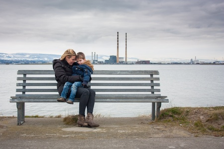 mother on bench: Mother and son sitting on bench with industrial backdrop Stock Photo