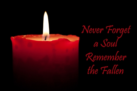Never forget a soul remember the fallen written next to a burning red candle Stockfoto