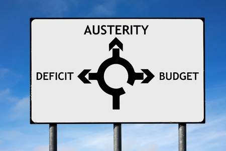 austerity: Road sign with roundabout directions pointing towards austerity deficit and budget to illustrate the financial crisis Stock Photo