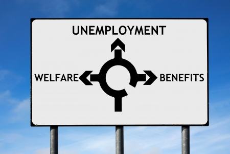 public welfare: Road sign with roundabout directions pointing towards unemployment welfare and benefits to illustrate the financial crisis